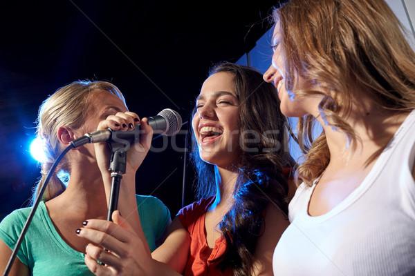 Boldog fiatal nők énekel karaoke éjszakai klub buli Stock fotó © dolgachov