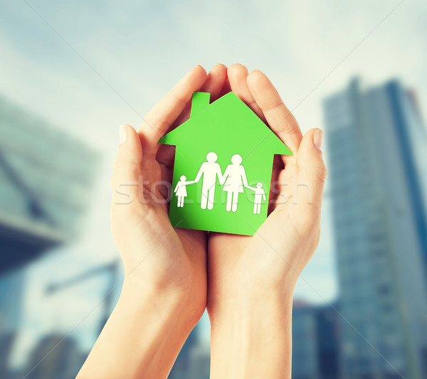 hands holding green house with family Stock photo © dolgachov