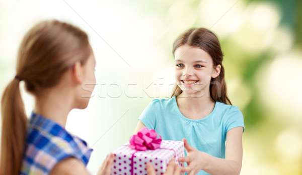 happy girls with birthday present over green Stock photo © dolgachov
