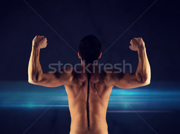 young man showing biceps and muscles Stock photo © dolgachov