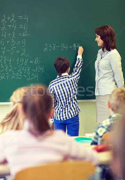 Nauczyciel uczeń piśmie kredy pokładzie edukacji Zdjęcia stock © dolgachov