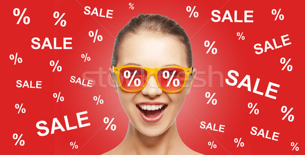 happy teenage girl in shades with sale signs Stock photo © dolgachov