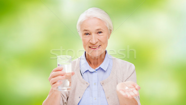 happy senior woman with water and medicine Stock photo © dolgachov