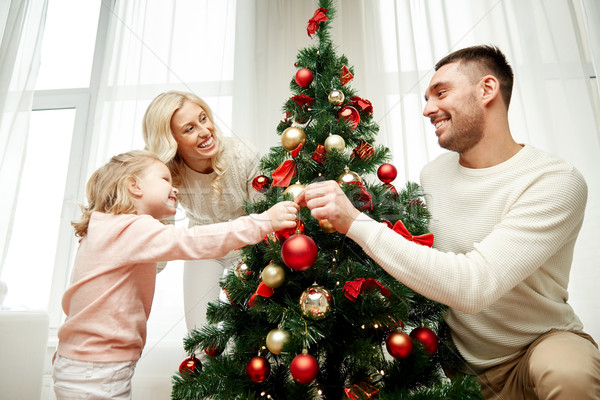 Stock photo: happy family decorating christmas tree at home