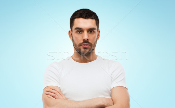 young man with crossed arms over blue background Stock photo © dolgachov