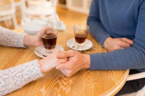 close up of couple holding hands at restaurant Stock photo © dolgachov