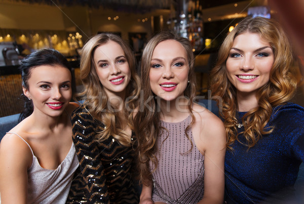 happy smiling women taking selfie at night club Stock photo © dolgachov