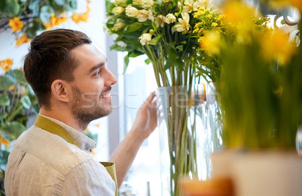 happy smiling florist man at flower shop Stock photo © dolgachov