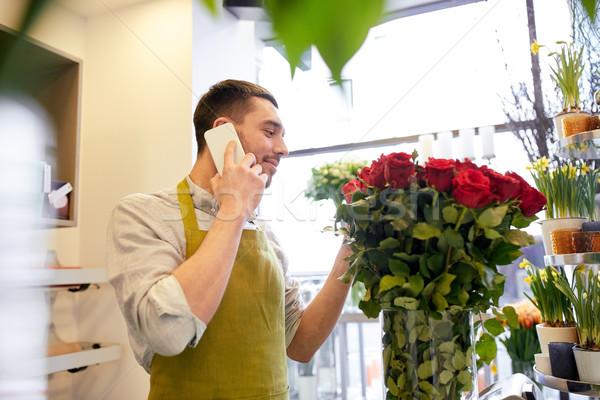 Férfi okostelefon vörös rózsák virágüzlet emberek vásár Stock fotó © dolgachov