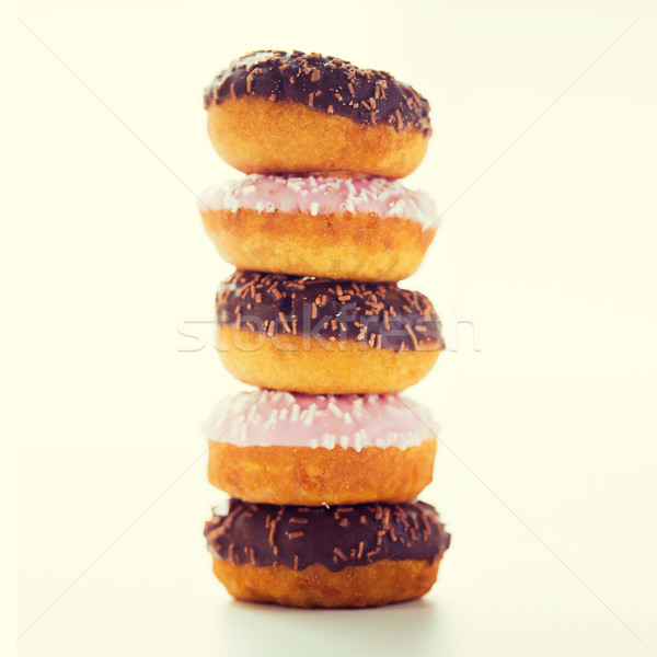 close up of glazed donuts pile over white Stock photo © dolgachov