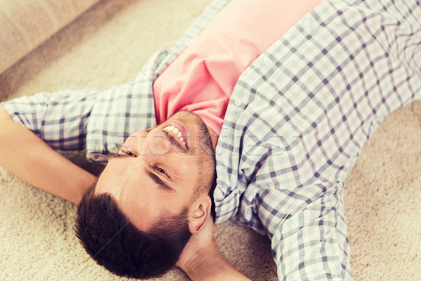 happy man lying carpet or rug at home Stock photo © dolgachov
