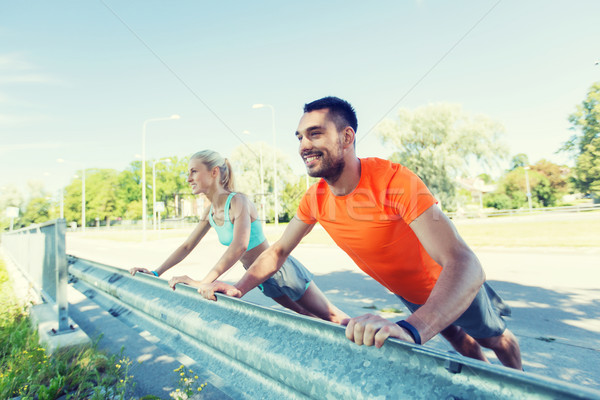 Stock photo: close up of happy couple doing push-ups outdoors