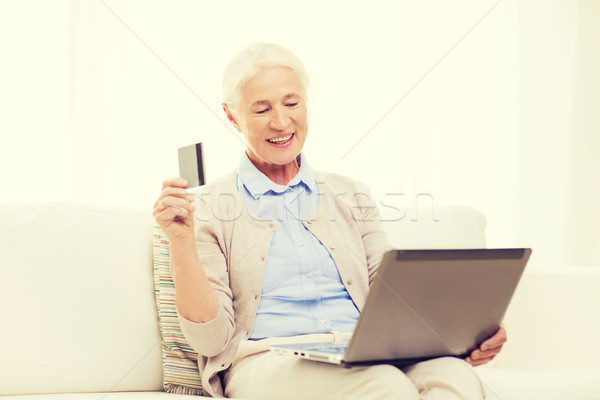 senior woman with laptop and credit card at home Stock photo © dolgachov