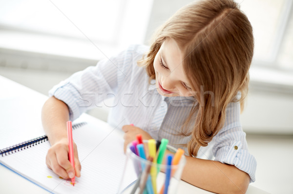 Stock photo: happy girl drawing with felt-tip pen in notebook