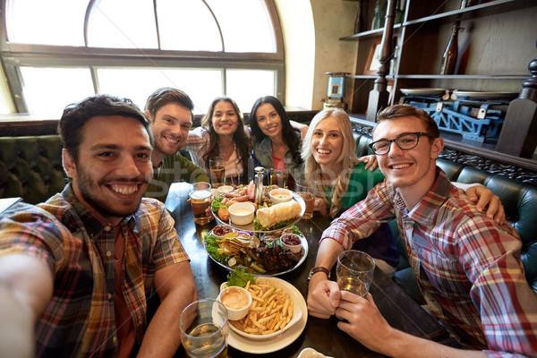 happy friends taking selfie at bar or pub Stock photo © dolgachov