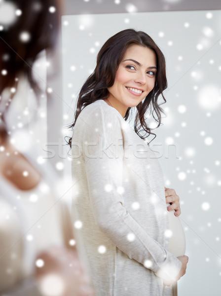 Szczęśliwy kobieta w ciąży patrząc lustra domu ciąży Zdjęcia stock © dolgachov