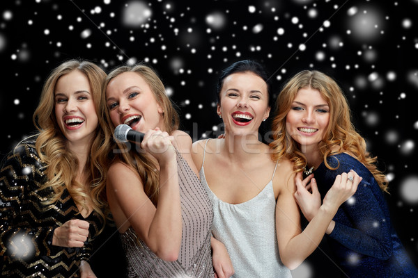 happy young women with microphone singing karaoke Stock photo © dolgachov