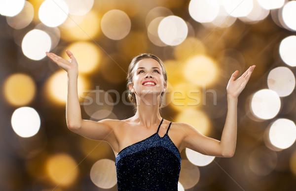 smiling woman raising hands and looking up Stock photo © dolgachov