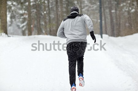 Stock photo: man running on snow covered winter road in forest
