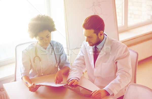 doctors with tablet pc and clipboard at hospital Stock photo © dolgachov