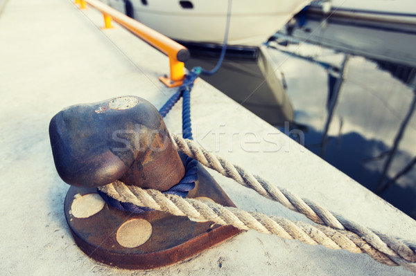 rusted iron mooring bollard with rope on pier Stock photo © dolgachov