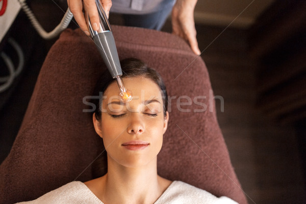 woman with microcurrent face massager in spa Stock photo © dolgachov