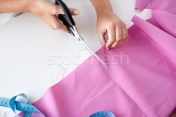 woman with tailor scissors cutting out fabric Stock photo © dolgachov