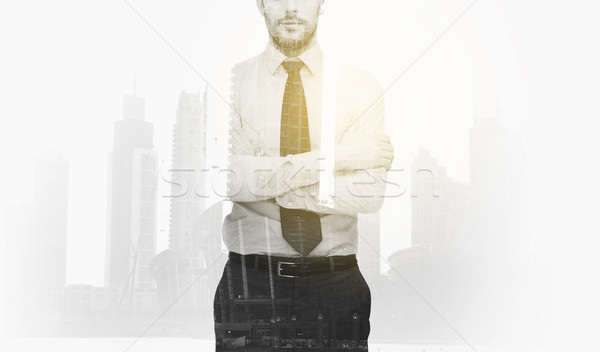 Stock photo: businessman with crossed arms over city buildings