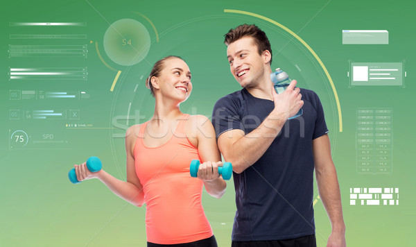 sportive man and woman with dumbbells and water Stock photo © dolgachov