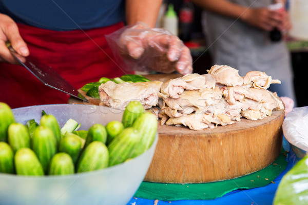 cook with poultry and cucumbers at street market Stock photo © dolgachov