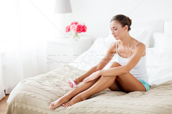 woman with epilator removing hair on legs at home Stock photo © dolgachov