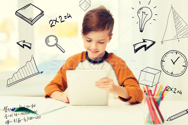 smiling boy with tablet pc and notebook at home Stock photo © dolgachov