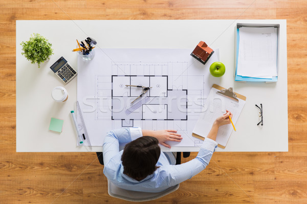 architect with blueprint writing to clipboard Stock photo © dolgachov