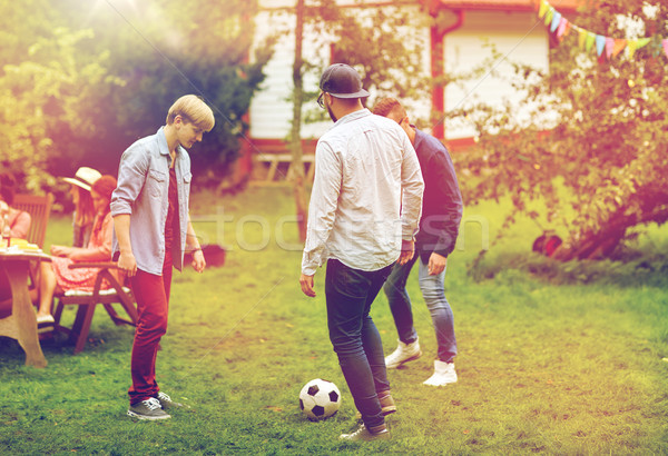 happy friends playing football at summer garden Stock photo © dolgachov