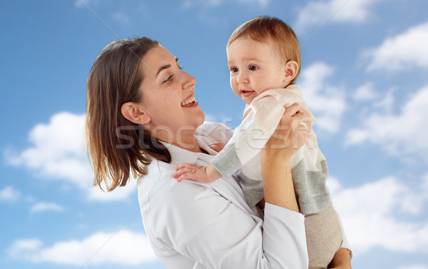 happy doctor or pediatrician with baby over sky Stock photo © dolgachov
