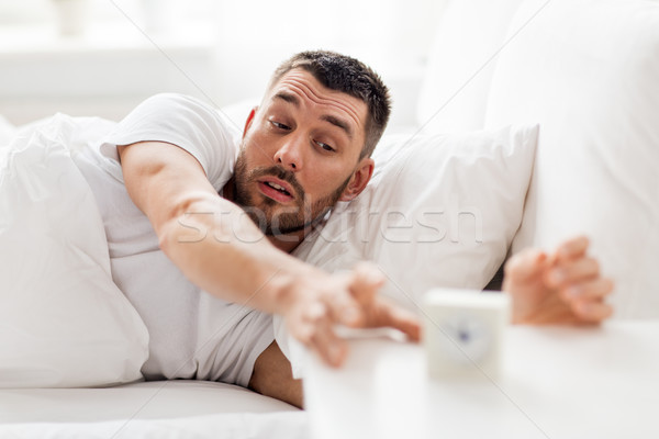 young man in bed reaching for alarm clock Stock photo © dolgachov