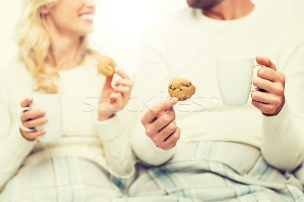 close up of happy couple with cookies and tea cups Stock photo © dolgachov