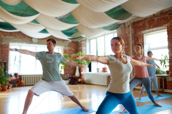 group of people doing yoga warrior pose at studio Stock photo © dolgachov