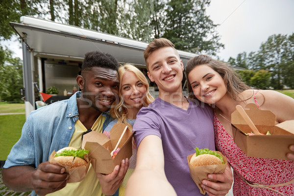 happy friends taking selfie at food truck Stock photo © dolgachov