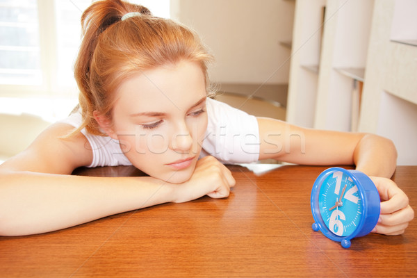 pensive teenage girl with clock Stock photo © dolgachov