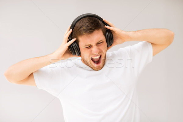 man with headphones listening loud music Stock photo © dolgachov