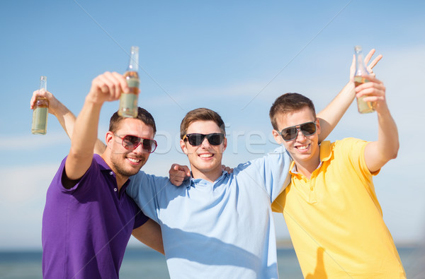 friends on the beach with bottles of drink Stock photo © dolgachov