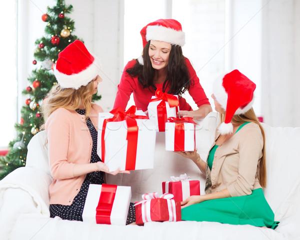women in santa helper hats with many gift boxes Stock photo © dolgachov