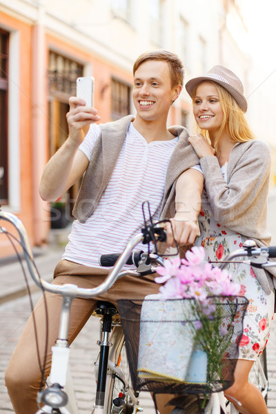 couple with bicycles and smartphone in the city Stock photo © dolgachov