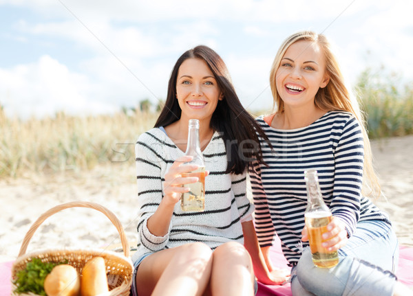 girlfriends with bottles of beer on the beach Stock photo © dolgachov