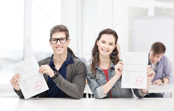 two teenagers holding test or exam with grade A Stock photo © dolgachov