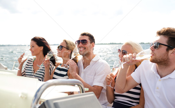 smiling friends with glasses of champagne on yacht Stock photo © dolgachov