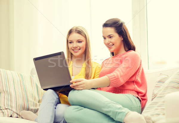 Stock photo: two smiling teenage girls with laptop at home