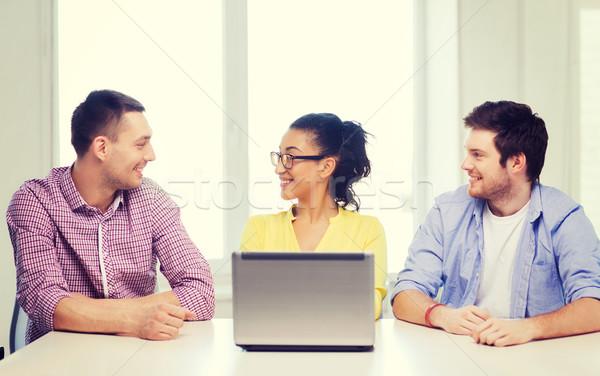 Tres sonriendo colegas portátil oficina educación Foto stock © dolgachov