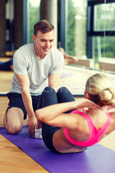 Stock photo: smiling woman with male trainer exercising in gym